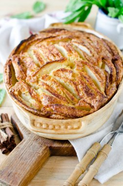 Apple pie with cinnamon on a wooden table
