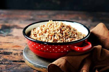 Boiled buckwheat with butter in a pan on a dark wooden background
