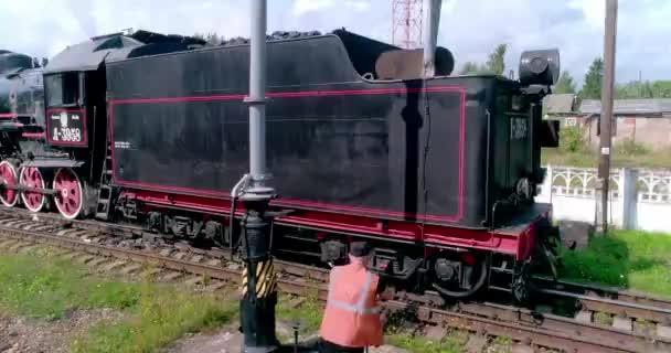 parní lokomotiva železnice, ostashkov, plnicí vodní uhlí, tendr, potrubí, železniční práce, bezpečnostní vesta, lokomotiva posádka, železnice, železnice, železniční stanice, železniční stanice, retro
