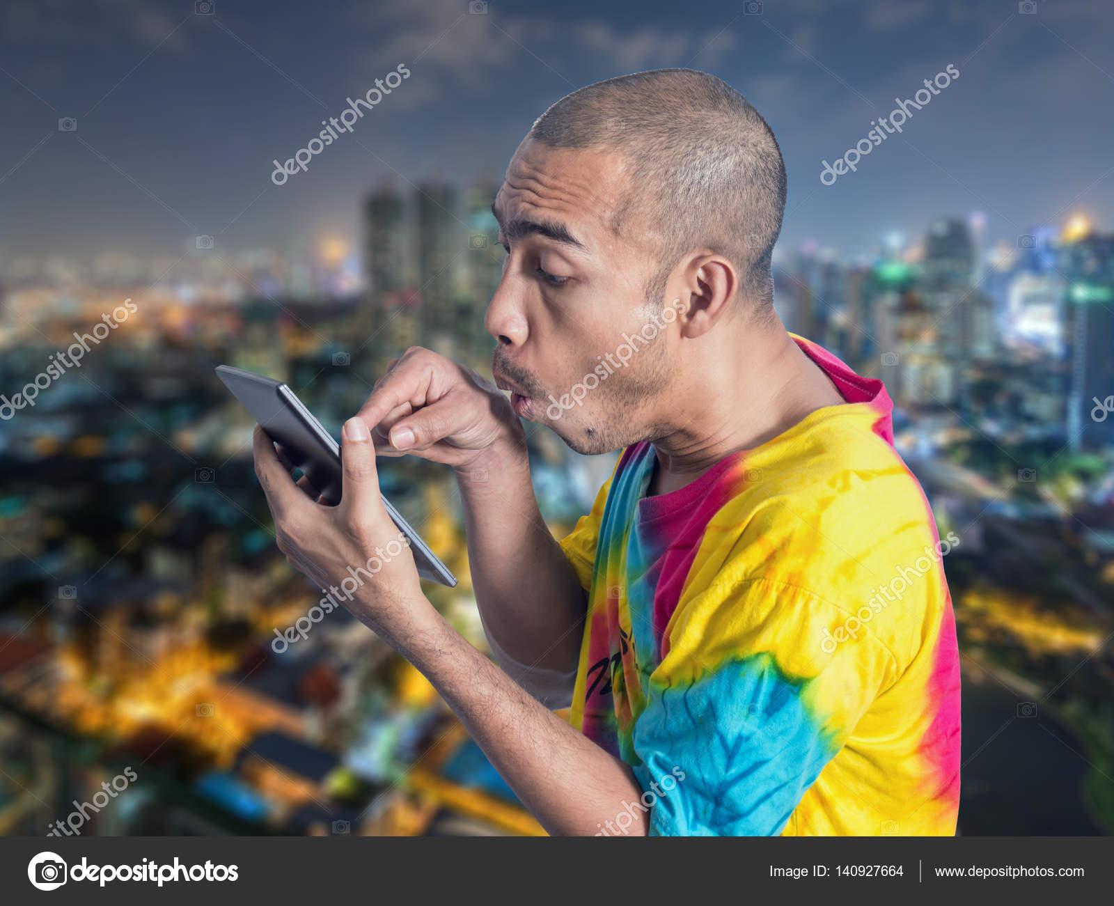 Asiatischer Mann, der digital-Tablette mit overacting auf Unschärfe ...
