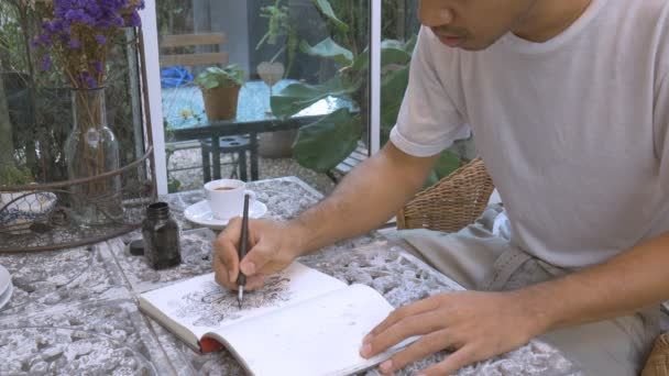 Asian man drawing doodle line art by black ink on paper in coffee bar