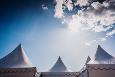 Peaks of three pyramidal white tents and blue sky background wit