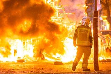 İtfaiyeciler bir Falla controllin Valenciana tarafından neden olduğu bir şenlik ateşi çevresinde