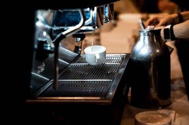 Woman preparing an espresso coffee at a coffee grinder in a rest