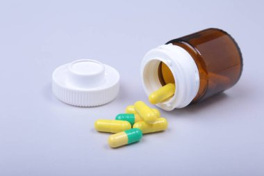Colorful medical pills and capsules on white table with space for text.