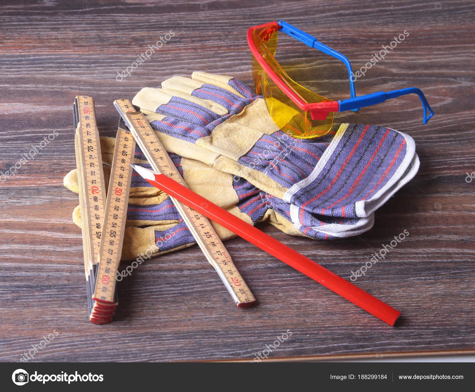 Casco naranja, gafas de seguridad, guantes, Sierra y medición cinta ...