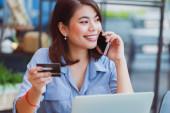 Asiatin benutzt Handy mit Kreditkarte und Laptop