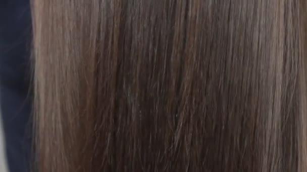 Použití hřeben na styl dlouhé hnědé ženské vlasy, close up video