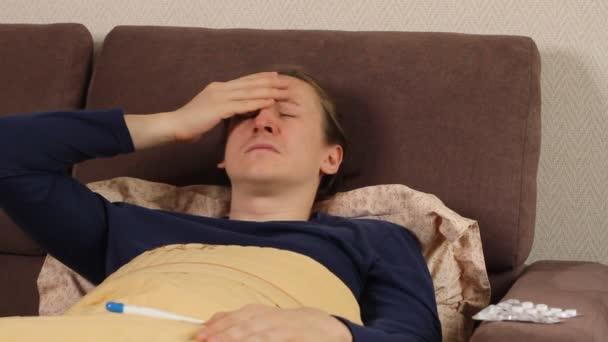 Kranker junger kaukasischer Hipster-Mann liegt hustet und niest im Bett. Erkältung und Grippe, hohe Körpertemperatur