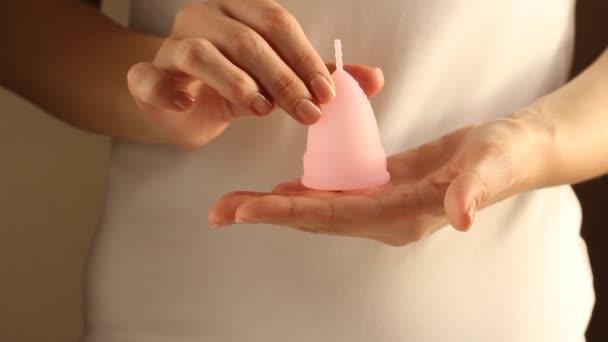 Detailní záběr mladé ženy v bílém tričku drží opakovaně použitelný růžový silikonový menstruační pohár