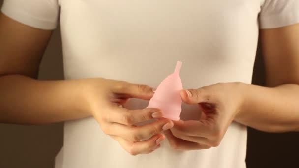 Nahaufnahme einer jungen Frau im weißen T-Shirt, die eine wiederverwendbare rosa Silikon-Menstruationstasse in der Hand hält