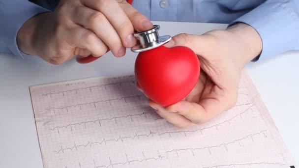 Kardiologe Arzt überprüft Herzfrequenz auf einem Spielzeug roten Herzen. Phonendoskop, Stethoskop und Kardiogramm. Gesundheitsfürsorge und Frühdiagnose.