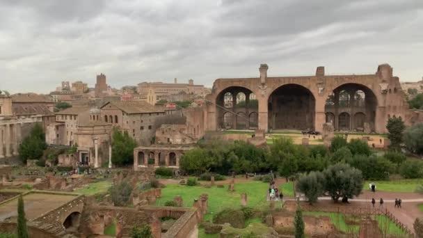 ŘÍM, ITÁLIE - 28. června2020. Starověké ruiny Forum Romanum. Turisté procházka přes římské fórum v centru Říma, Itálie v deštivý den. Historická evropská architektura.