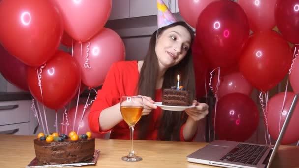Fiatal női blogger szülinapi kalapban, aki laptoppal beszélget, kezében egy szelet tortával, gyertyával. Boldog születésnapot nő egyedül otthon az online konferenciahívás vagy élő streaming modullal
