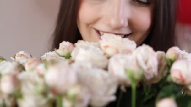 Caucasian woman enjoys her bouquet of flowers. Young brunette woman sniffs white roses flowers aroma and smiling, close up view.