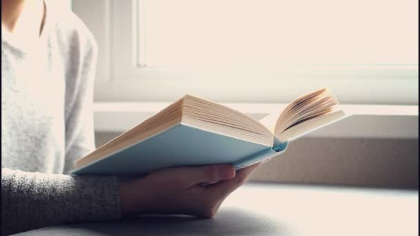 Mladá žena čtení knihy v obývacím pokoji, otočit stránku, učení, studium, vzdělávání, číst knihy, zůstat doma koncept.