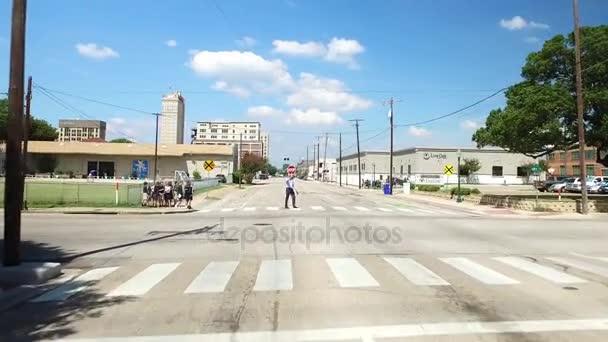 Jízdy v centru města Waco Texas jako školní děti přes ulici