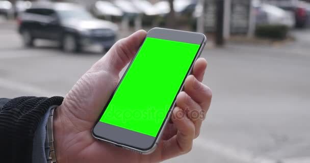 Muž drží zelená obrazovka Smartphone ve městě