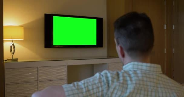 Muž hodinky zelená obrazovka Tv v hotelovém pokoji luxusní