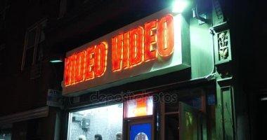 Night Establishing Shot of Video Store in Big City
