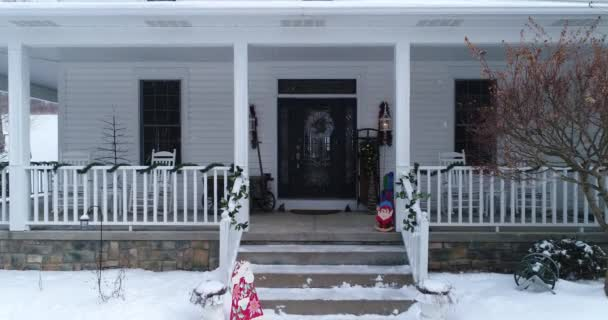 A personal perspective slowly approaching the front door of a house and porch decorated for Christmas.