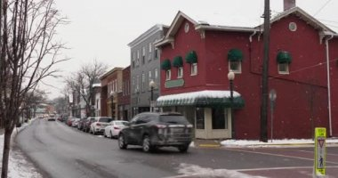 A daytime winter exterior establishing shot of a generic small town's Main Street shopping district storefronts and traffic. Store marquees digitally removed for customization. Snowing version. Pittsburgh suburbs.
