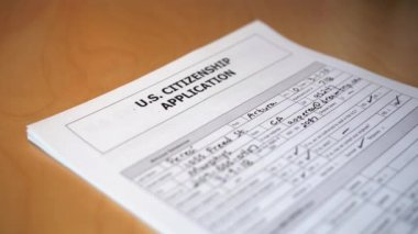 A slow motion shot of a United States immigration citizenship application being denied. Fictitious information on form. Shot at 60fps.