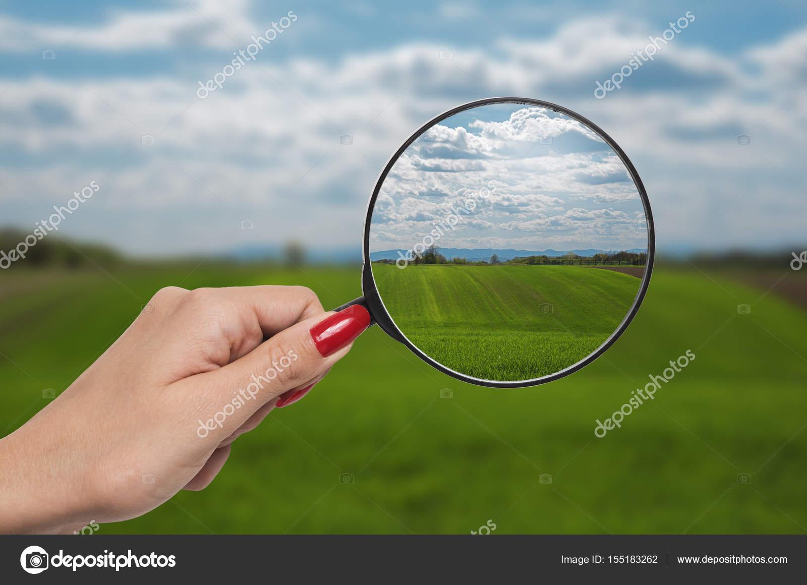 A fókusz természet megművelt területek és a kéz tartja egy nagyítóval bb5d6731ff