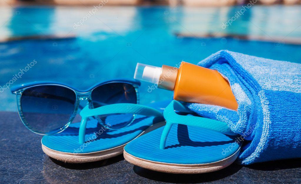 35cf3fb627 Gafas de sol con crema de protección solar, zapatillas azules y toalla a  bordo —