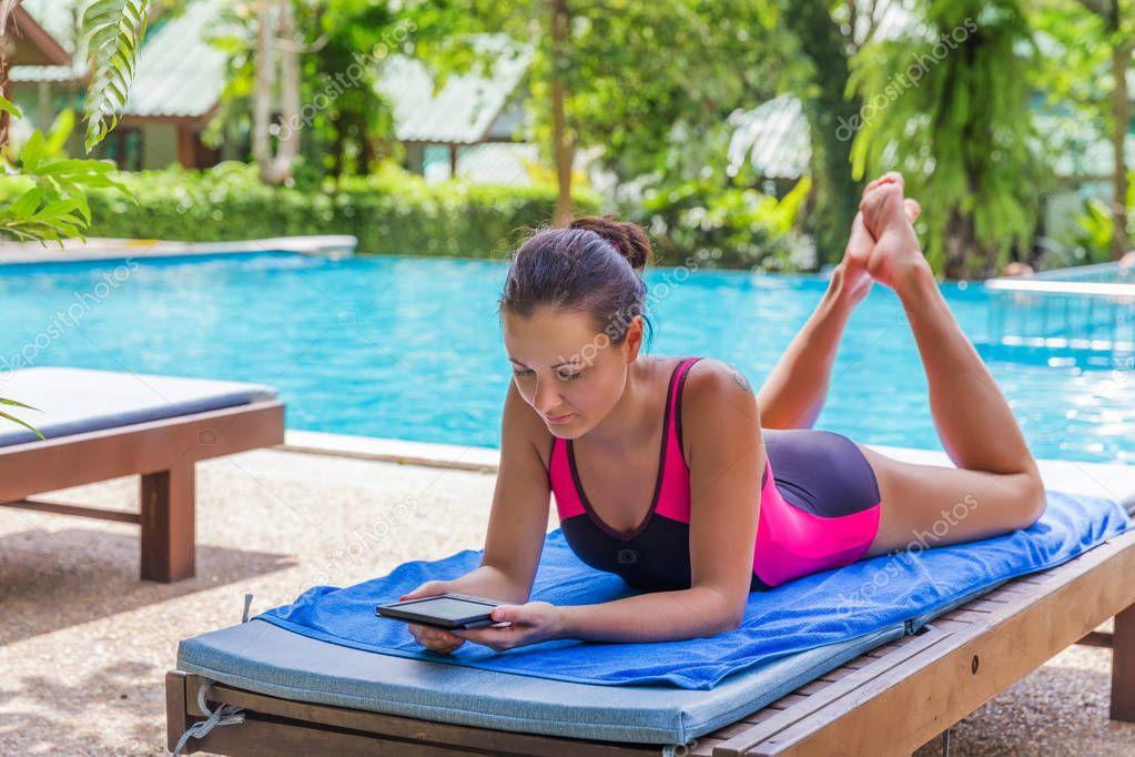 brunette woman read electronic book near pool