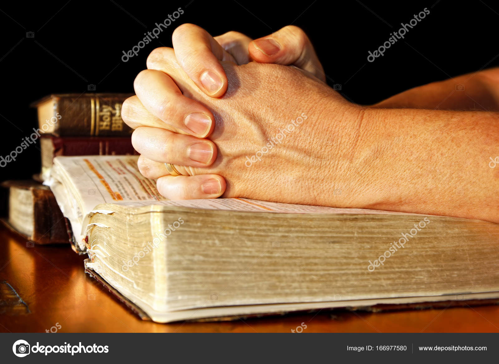 praying hands in light with holy bibles — stock photo © lincoln