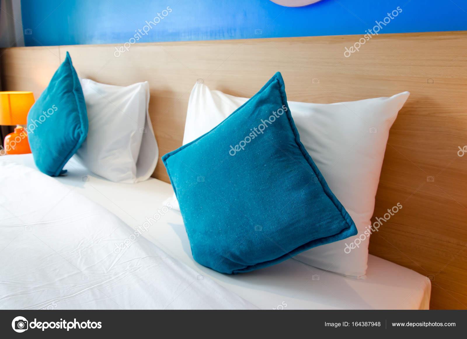 Blauw kussen op het bed u stockfoto aoo
