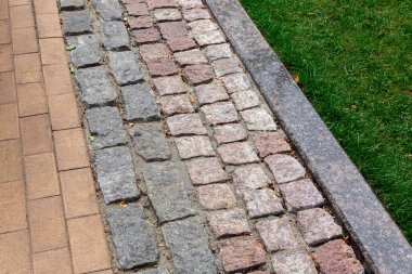 a pedestrian pavement made of stone and granite tiles with a curb near a green lawn in the park, close up.