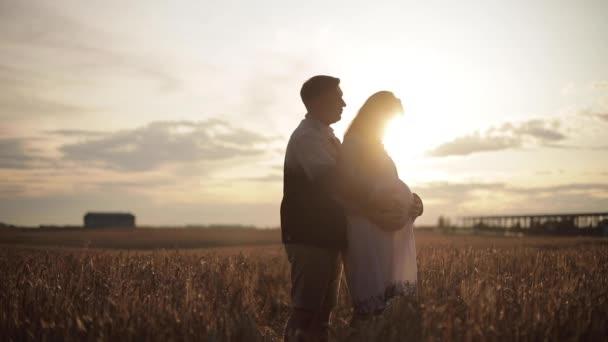 Mosolygó férj gyengéden öleli terhes feleségét a szabadban