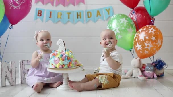 Two cute little baby boy and girl eating festive cake celebrating happy birthday