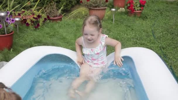 Little sisters playing in inflatable pool.