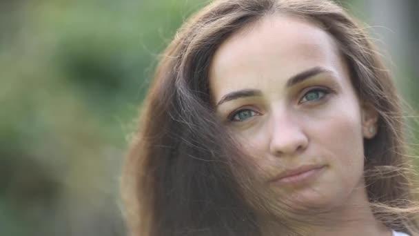 Zblízka úsměv tvář brunetky mladé ženy s dlouhými vlnitými vlasy pózovat venku