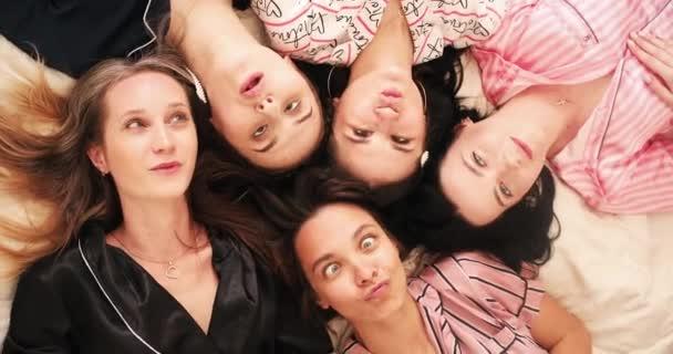 Mosolygó csinos női barátok grimaszolnak az ágyban