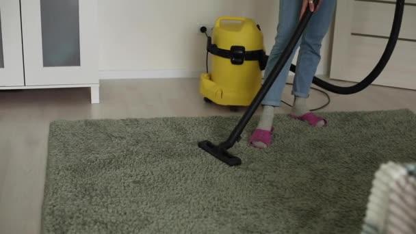 Žena vysává podlahu a koberec doma, čistí od bakterií