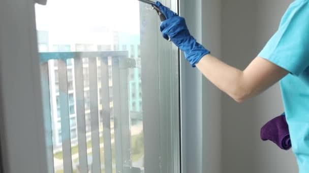 Frau putzt Fenster. Archivvideo einer anonymen Hausfrau oder Putzfrau, die das Fenster mit einem Rakel wäscht.