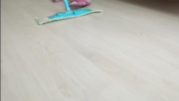 Dáma utírá podlahu v kuchyni mopem
