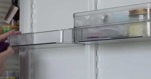 Woman is washing inside fridge at home