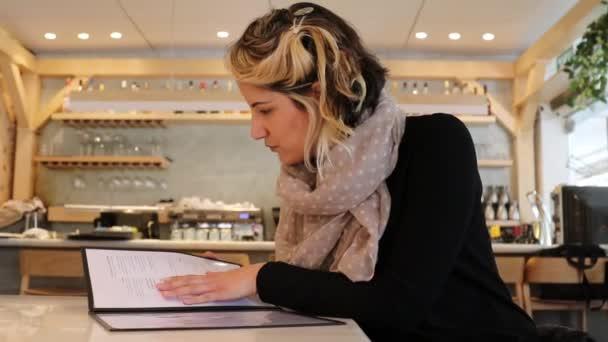 Žena hledá možnosti v menu v restauraci