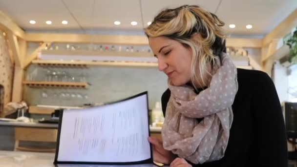 Žena čte menu v restauraci
