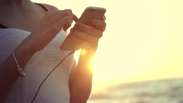 Lövés a fiatal, vonzó nő gazdaság smartphone a strandon