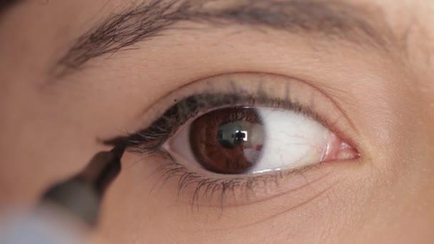 Shot z makro záběr ženy použít oční linky v pomalém pohybu