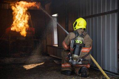 İtfaiyecinin arkadan görünüşü yangın koruma giysisi giyip yangın söndürme odasına giriyor ve itfaiye istasyonunda su püskürtüyor. Eğitim yangın tatbikatı.