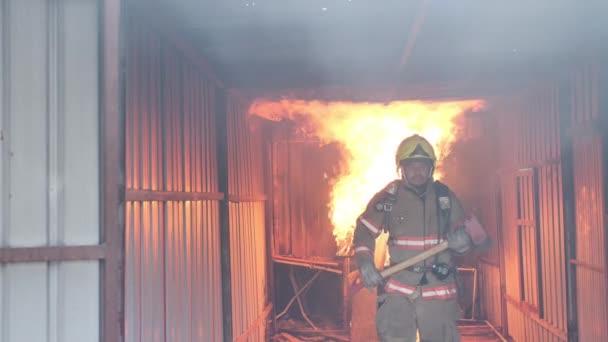 Asijský hasič chodí sebevědomě drží sekeru s ohněm hoří tvrdě v pozadí. Koncept kariéry hasiče. Zpomalený pohyb.