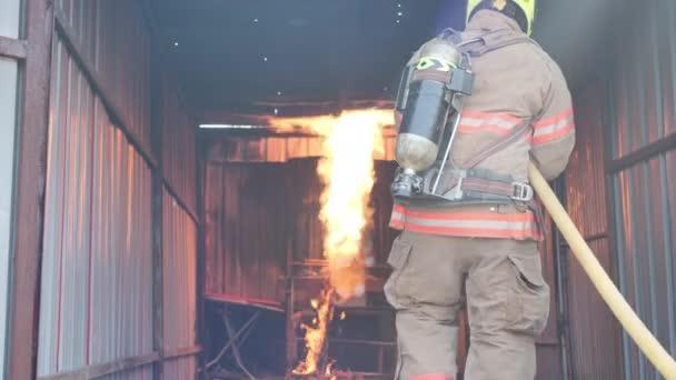 Zadní pohled na hasiče nosit protipožární oblek kráčející do požární výcvikové místnosti a stříkací vody Požár na požární stanici Pomalý pohyb. Hasičská kariéra, Požární cvičení koncepce.