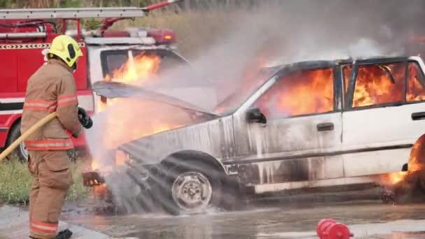 Asijský hasič nosí protipožární oblek. Hasič bojující s ohněm na autě při požárním cvičení Dopravní nehoda na hasičské stanici, koncepce hasičské kariéry. Zpomalený pohyb